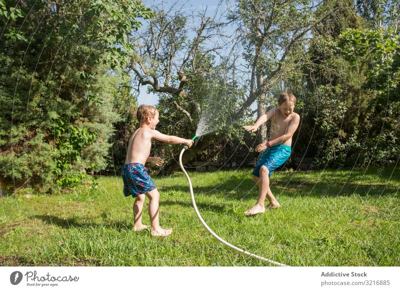 Little kids in swimwear having fun with splashing water children summer playing happy lifestyle leisure recreation holiday childhood joy enjoyment amusement
