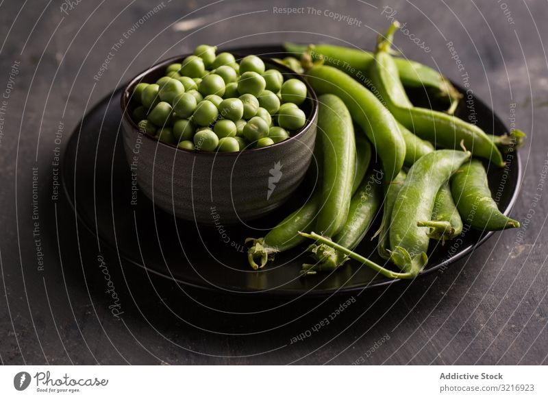 Fresh peas and pea pods on dark background bowl ecological food fresh green healthy legume natural organic raw seed vegetable vegetarian harvest nutrition sweet