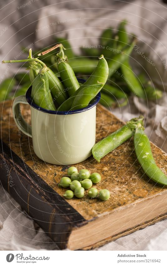 Fresh peas and pea pods bowl cup ecological food fresh green healthy legume natural organic raw seed vegetable vegetarian white cream wooden plant towel salt