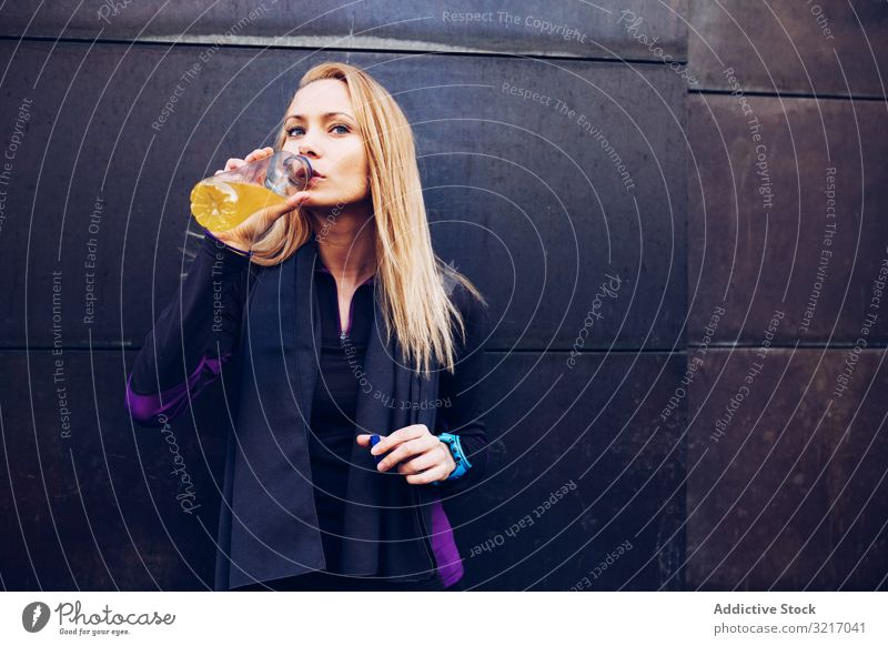 Woman drinking isotonic drink while resting active athletic beautiful blonde body cardio caucasian exercise fitness gym healthy jog lifestyle outdoors runner