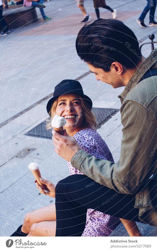 Happy couple feeding each other by ice cream happy cheerful woman cornet girlfriend boyfriend eating food fun lifestyle love dating flirting having fun
