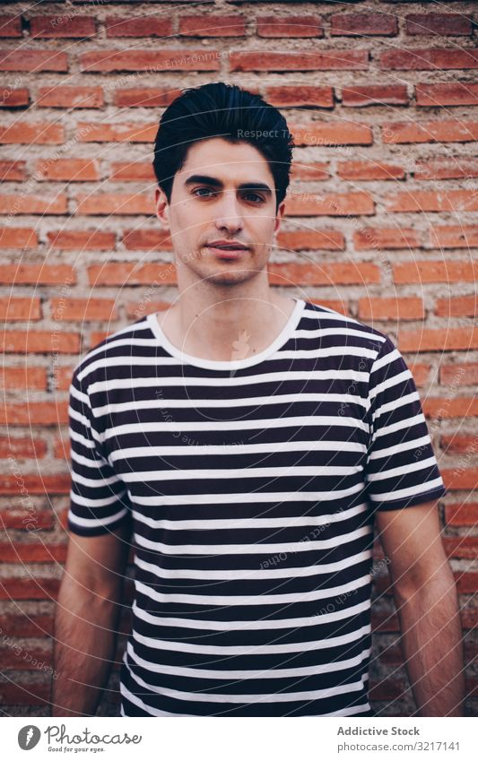 Portrait of casual young man attractive portrait lifestyle guy stylish stripped t-shirt handsome trendy person caucasian modern urban posing brick wall