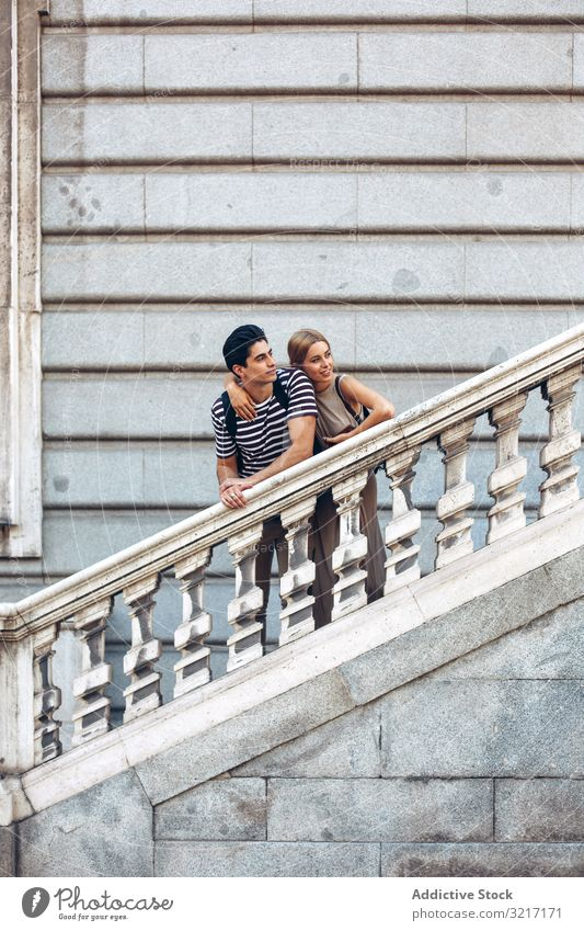 Young couple standing on ancient stairs against wall admiring young old building historical attractive love woman romance relationship architecture railing