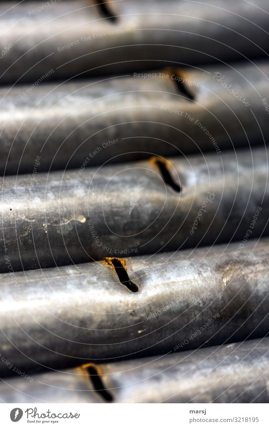 Galvanized iron tubes with slots Iron Iron-pipe Slit Rust zinc-plated Exterior shot worn-out sorted out Parallel Shallow depth of field Dented Scrap metal