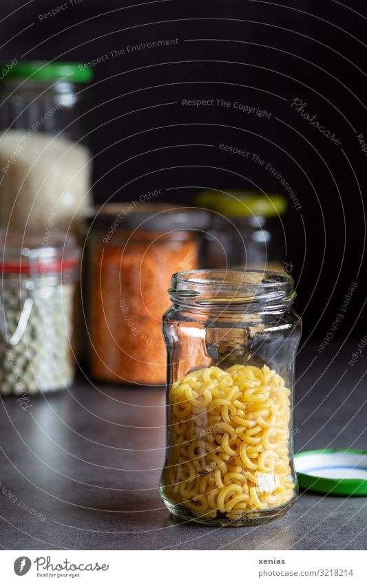 open glass container with pasta stands on a grey smooth worktop Food Grain Dough Baked goods Noodles Peas Lentils Nutrition Glass Screw top Glass container
