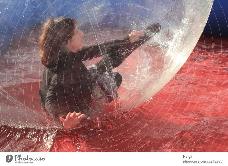 Woman with brunette long hair moves in a big plastic ball in a water basin Human being Feminine Adults 1 45 - 60 years T-shirt Skirt Hair and hairstyles