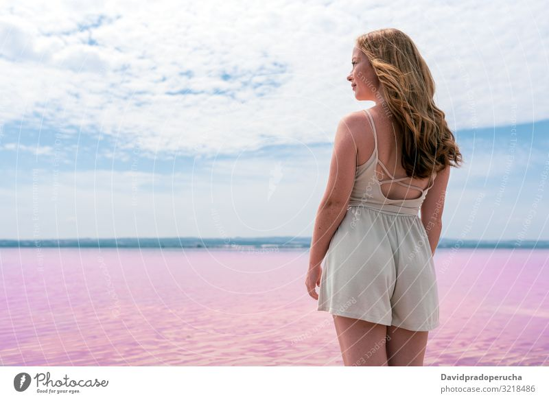 Back view of cute teenager woman wearing summer clothes on pink lake Alicante Spain beach beautiful blue sky coast coloration colorful cool copy space dress