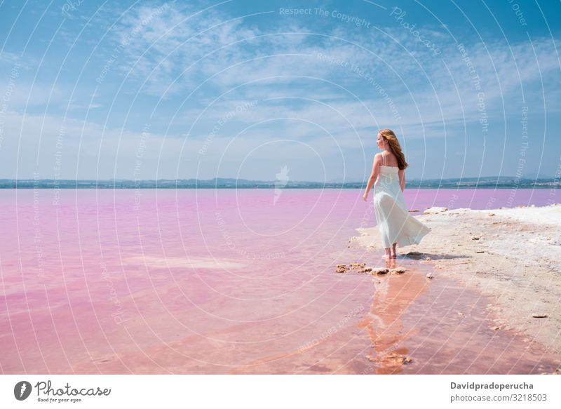 Back view of cute teenager woman wearing white dress walking on a amazing pink lake young saline romantic tourism summer happy alone sea colorful nature water