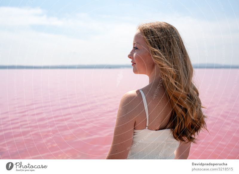 Side view of cute teenager woman wearing summer clothes standing on an amazing pink lake young romantic white freckles happy alone sea colorful adolescent water