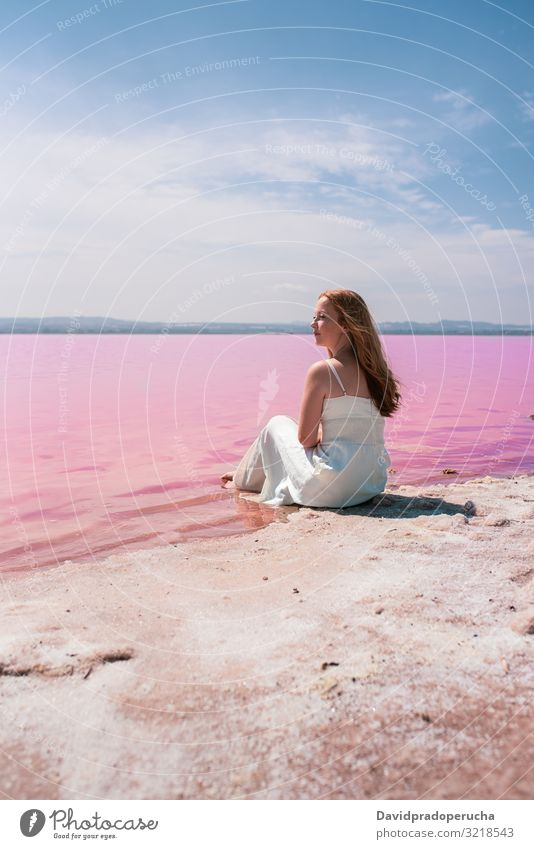 cute teenager woman wearing white dress sitting on an amazing pink lake young saline romantic tourism summer freckles happy alone sea colorful water copy space