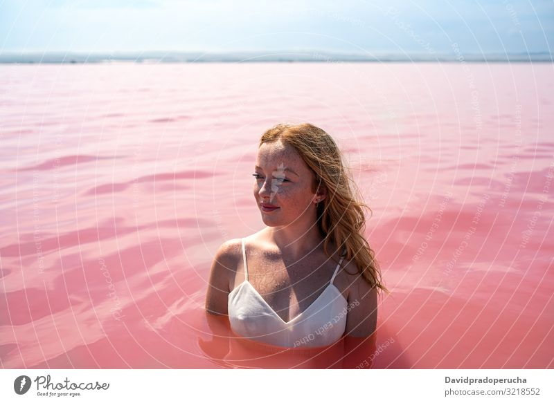 cute teenager girl wearing white dress in the water of an amazing pink lake woman stroll salty harmony mood romantic peace relax rest natural torrevieja