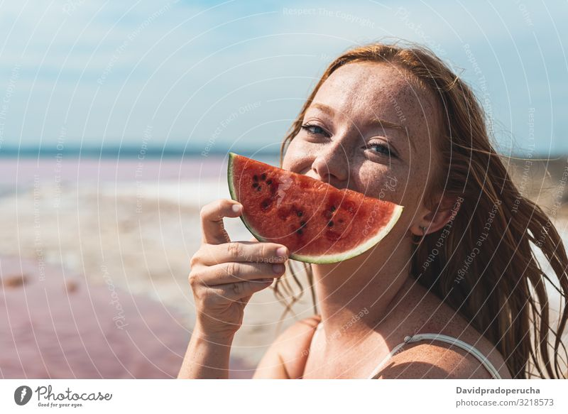 cute teenager woman covering face with watermelon smiling portrait red head looking at camera ginger pretty happiness Spain freckles girl freckled beach