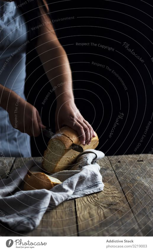 Crop woman cutting bread table rustic wooden old knife loaf fresh napkin food female healthy meal lunch dinner kitchen preparation piece slice lady lumber