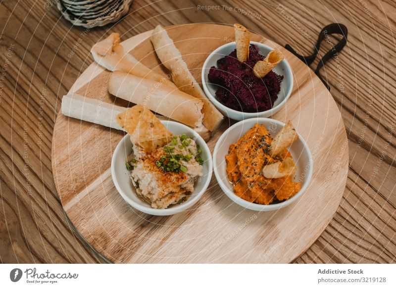 Different tasty sauces on round wooden stand dip vegetable crispy restaurant gourmet organic nutrition breakfast refreshing raw delicious holiday bread meeting