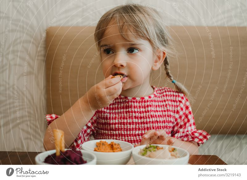 Girl eating with hand assorted food at table girl bowl gourmet homemade organic nutrition tasty refreshing raw adorable delicious yellow holiday innocence
