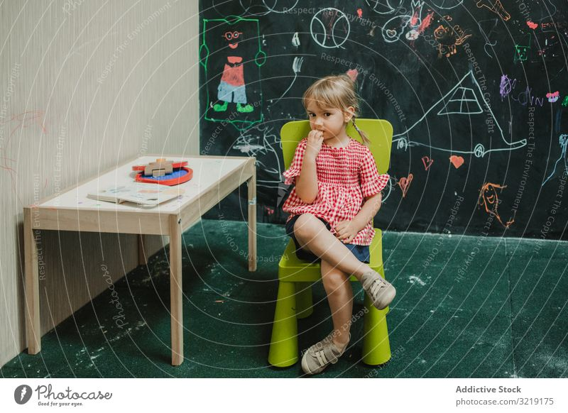 Girl sitting on light green chair with crossed legs child girl adorable childhood creative little creativity education fun kid learning play happy cute colorful