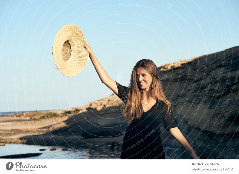 Cheerful woman holding hat in air model cheerful beach nature smile stylish young attractive beautiful pretty summer female natural elegant posing travel