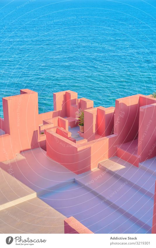 Pink wall construction against blue sea pink architecture building geometric structure urban facade abstract sky maze public exterior innovation modern city