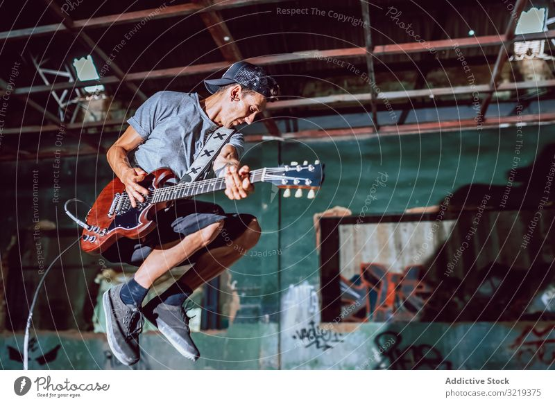 Musician playing electric guitar in abandoned place man musician jump grunge metal performance graffiti heavy rebel instrument young entertainment broken dark