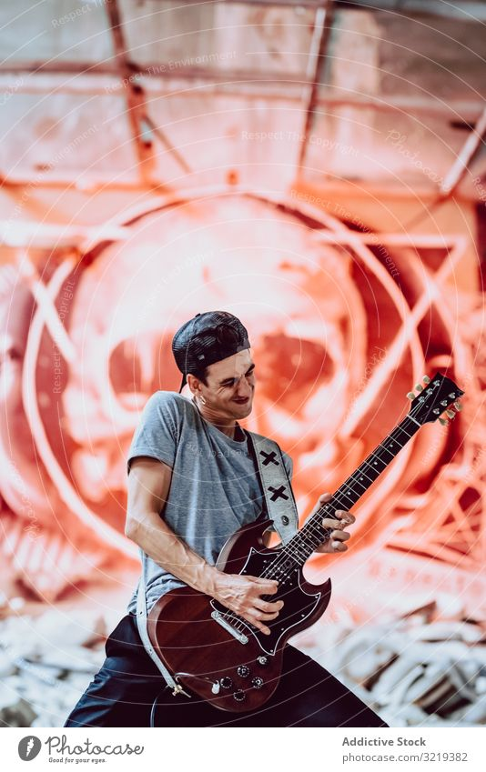 Musician playing electric guitar man musician grunge rebel metal instrument entertainment abandoned graffiti skull male lifestyle performer heavy sound rock