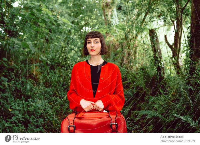 Woman in red with big red suitcase in forest woman travel stylish green female luggage nature beautiful bag piercing waiting freedom alone trip journey bush
