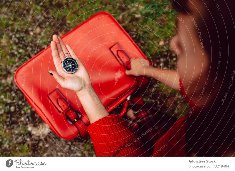Woman with red suitcase on ground checking compass destination orienteering baggage packing woman vacation travel young holiday location navigation journey
