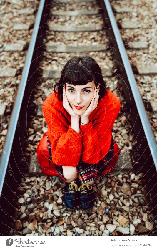 Woman sitting on sleepers in middle of railway woman railroad suitcase red travel stylish green female luggage nature beautiful bag waiting freedom alone trip