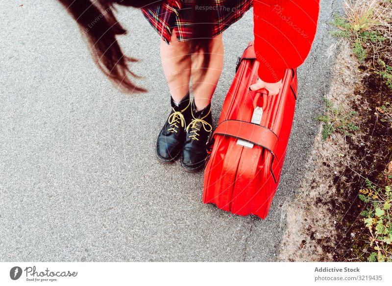 Woman in stylish boots with red suitcase standing on road woman legs travel luggage nature beautiful bag waiting freedom alone trip journey design tourist