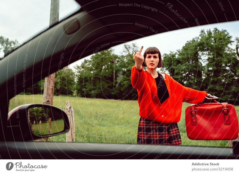 Woman in red sweater gesturing near car on road woman auto stop suitcase travel stylish female luggage nature beautiful bag fashion waiting freedom alone smile