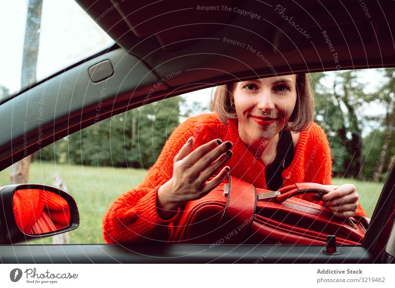 Woman putting suitcase in front window of car woman red road travel stylish female luggage nature beautiful bag fashion waiting freedom alone smile trip journey