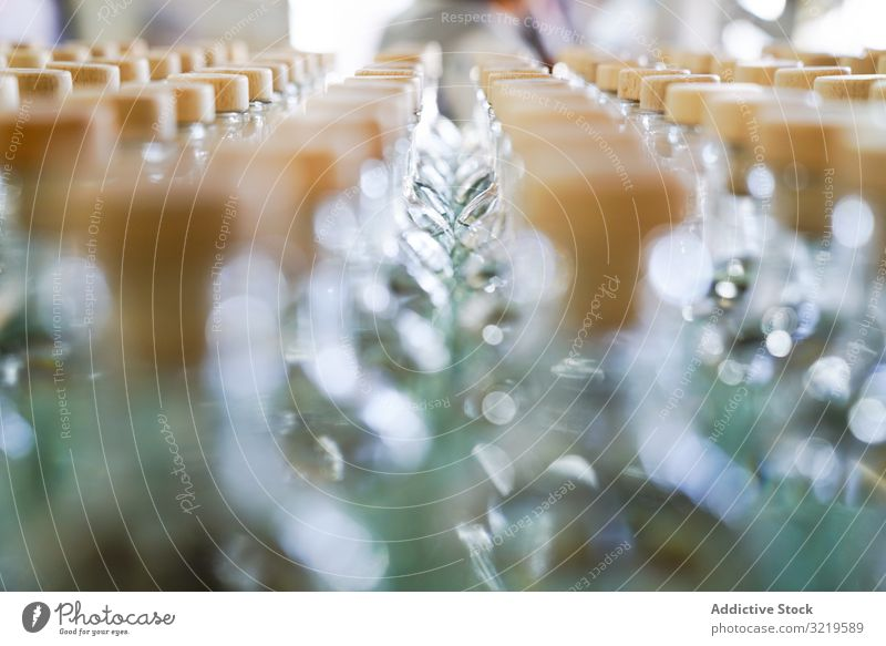Rows of unopened glass bottles row blurred lid daylight shiny drink alcohol modern distilled traditional beverage exotic technology industrial factory