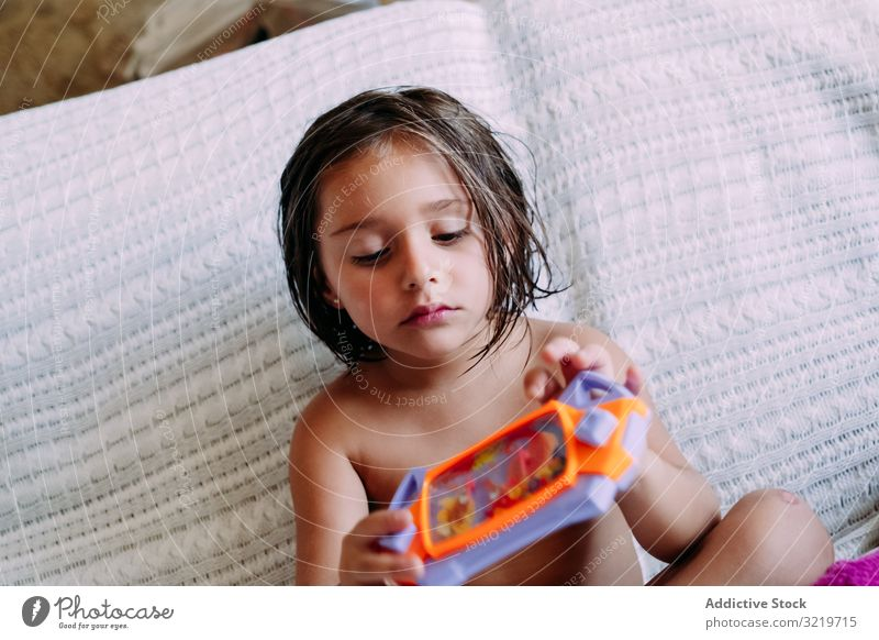 Child sitting on the couch kid sofa home child fun childhood lifestyle room cute little modern small barefoot casual enjoying lovely contemporary concentration