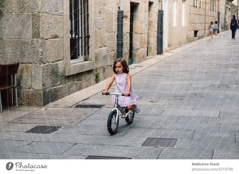 Girl riding on bicycle in narrow street smiling bike summer girl happy fun sport city cheerful day active childhood urban cyclist holiday lifestyle joyful dress