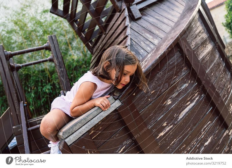 Smiling girl climbing onto wooden playground child fun activity kid smile sport happy little entertainment park brave lifestyle playful courageous support