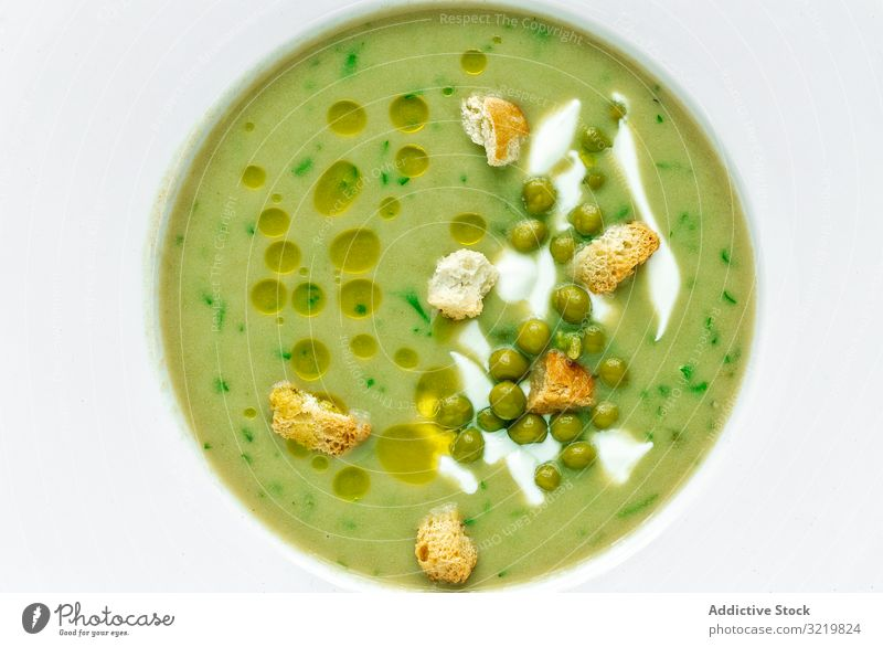 Green vegetable cream soup with peas and crackers green summer aromatic traditional tasty veggie meal food delicious vegetarian gourmet fresh ingredient orange
