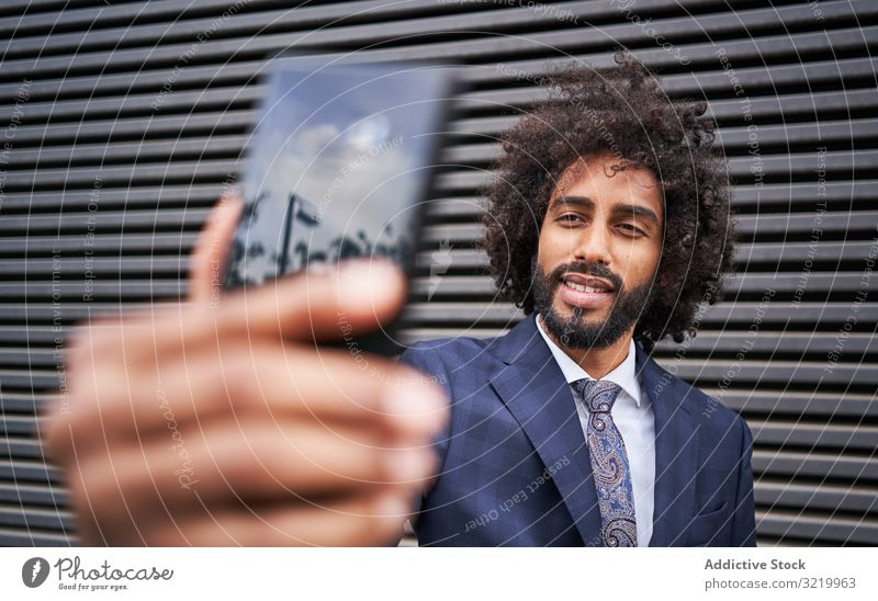 Joyful ethnic man taking selfie and smiling modern businessman formal african black smartphone wall smile happy afro cheerful african american office suit curly