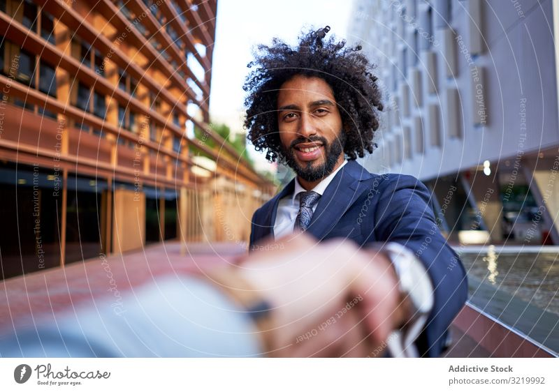 Ethnic happy businessman shaking hands with partner and looking at camera ethnic modern formal african black deal handshake agreement meeting partnership
