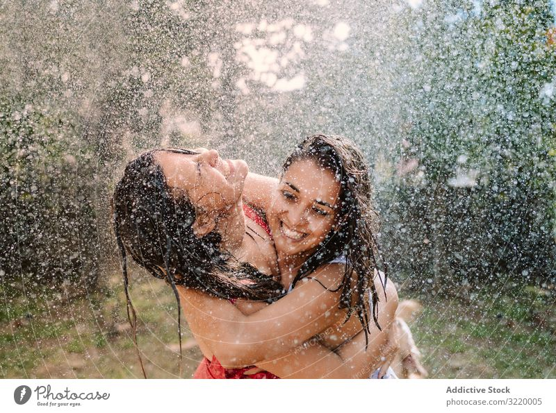 Friends in swimsuits hugging under water drops women splash garden friend girlfriend holiday fall summer hose fun cheerful joy friendship bonding together