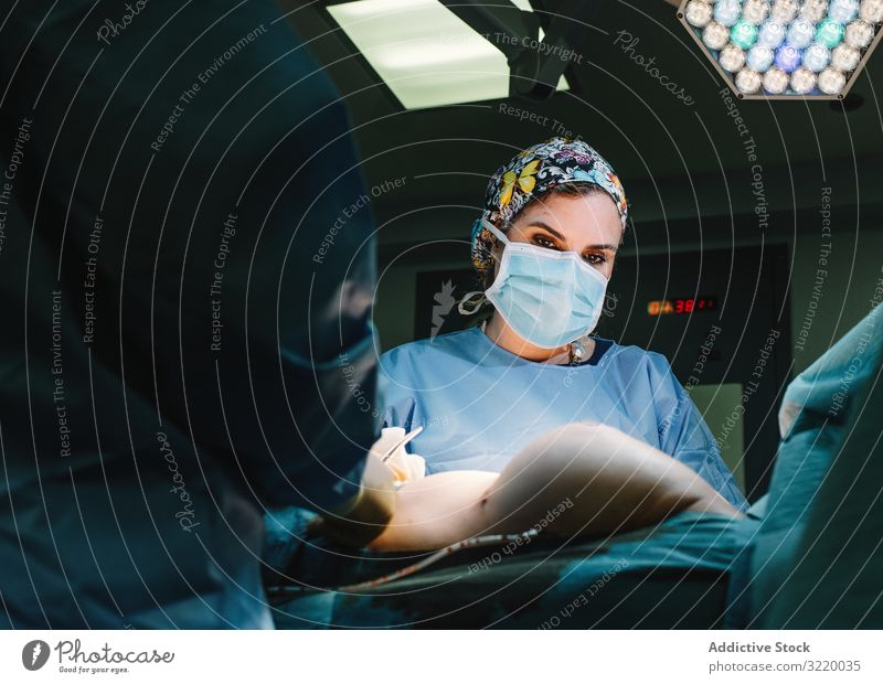 Concentrated female surgeon at work woman doctor surgery hospital operation medicine profession concentration young serious attentive surgical gown blue cap