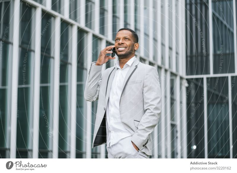 Elegant black man talking smartphone near building walking business architecture suit professional ethnic exterior african surfing corporate using futuristic