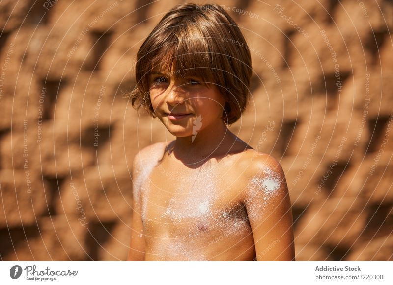 Boy with sunscreen on the body looking at the camera kid cream sunblock boy summer beach protection vacation care help childhood family apply suntan leisure