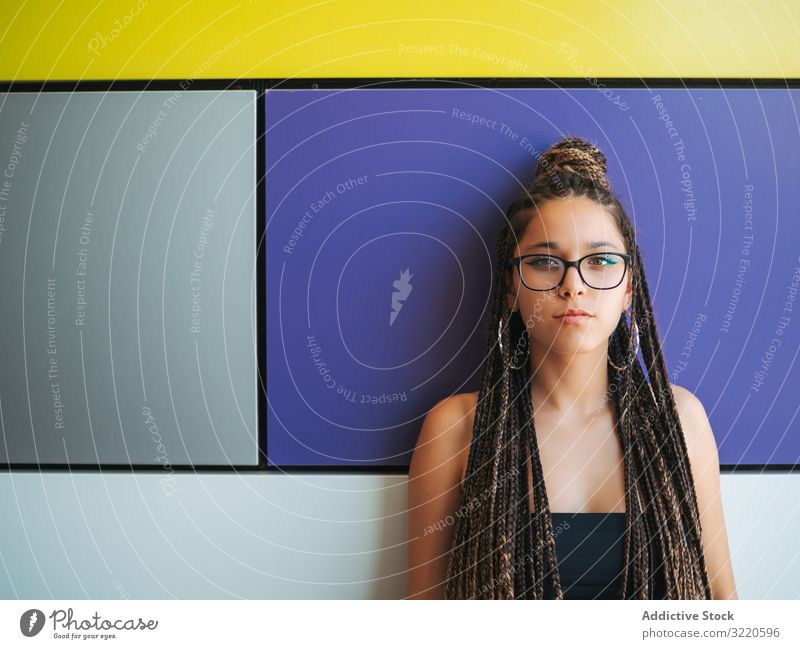 Charming teenage girl with braids in sunglasses nearby colorful wall earrings charming braided stylish teenager fun attractive fashion beautiful smart casual