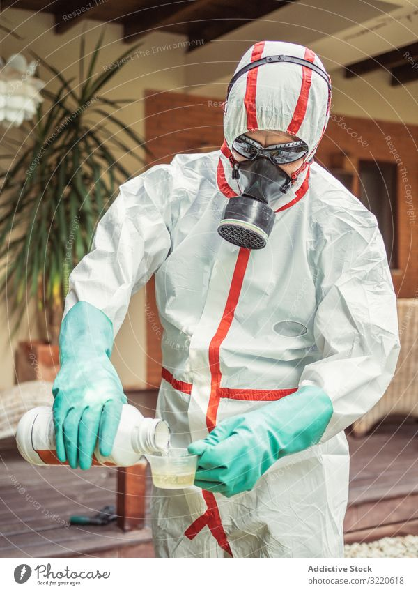 Man in suit for fumigation pouring chemical into tank man fumigator respiratory pesticide poison insect disinfection yard mask plant protection mosquito