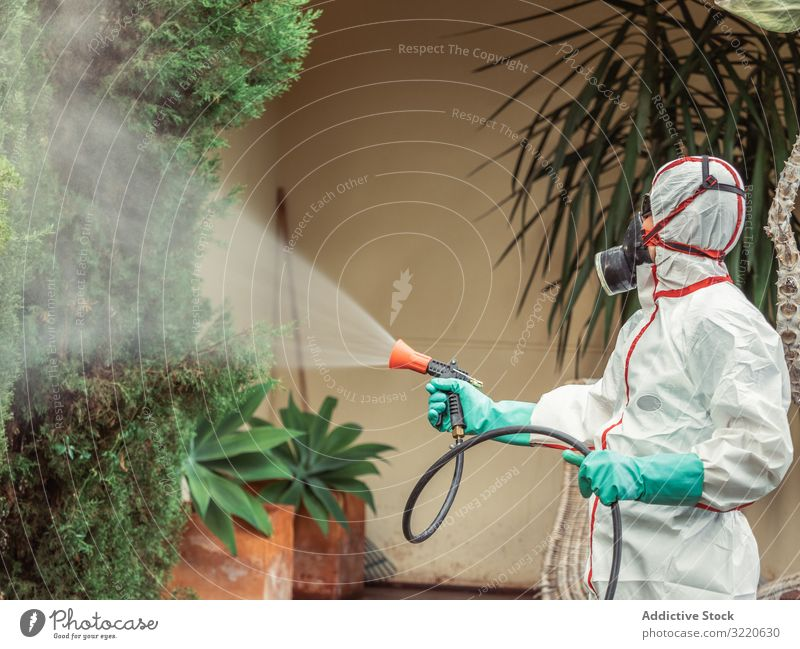 Fumigator in white uniform spraying substance on garden man fumigator trees bushes respiratory pesticide poison insect disinfection yard fumigation mask plant
