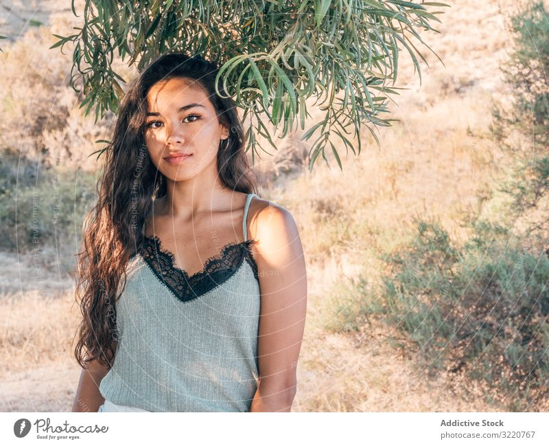 Playful trendy young ethnic woman in deserted countryside modern casual cactus sandy dry bush sunlight adult brunette attractive stylish hipster summer