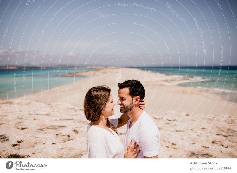 Loving couple embracing on coastline Formentera balearic islands Spain embrace seashore beach ocean romantic seaside nature relationship summer weekend