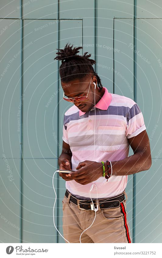 young cuban with afro hair using his cell phone, havana - cuba Lifestyle Happy Island Human being Masculine Young man Youth (Young adults) Man Adults Body Head