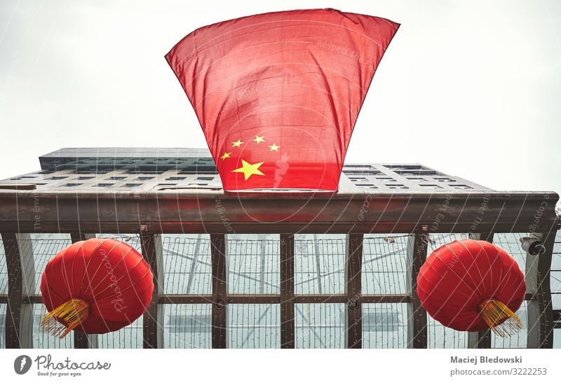 Looking up at Chinese flag and red lanterns on a building. Sky Wind Town Building Roof Flag Flying Red Symmetry Future Symbols and metaphors China Lantern