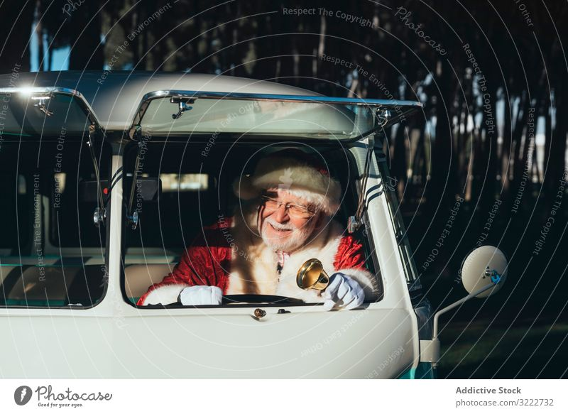 Cheerful Santa Claus with bell in van santa driver christmas holiday man event celebration vehicle transport senior male cheerful positive bearded gray-haired