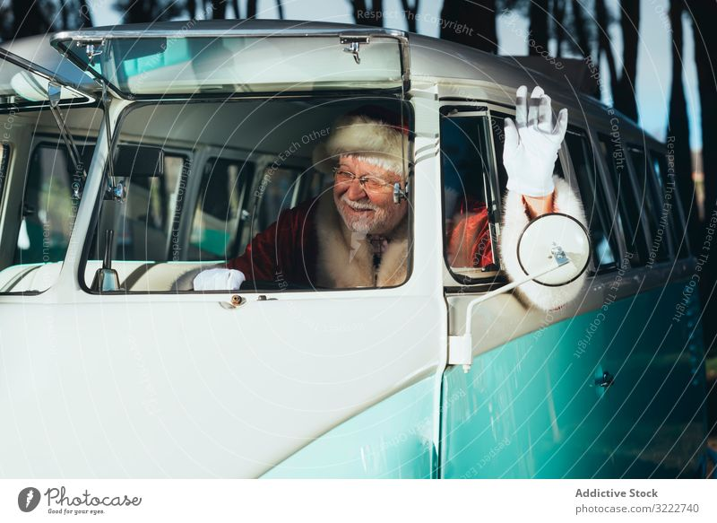 Santa Claus waving from old van santa holiday man christmas event celebration vehicle transport senior male cheerful bearded gray-haired traditional costume